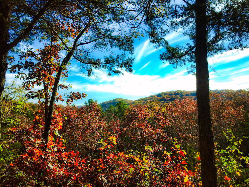 The Ozarks: Don't even think about putting a filter on this gorgeousness, which features rolling, green mountains peeking out from behind some red foliage. Credit Nancy/Flickr.