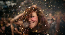 A Girl Dancing Under A Confetti Rain At A Festival