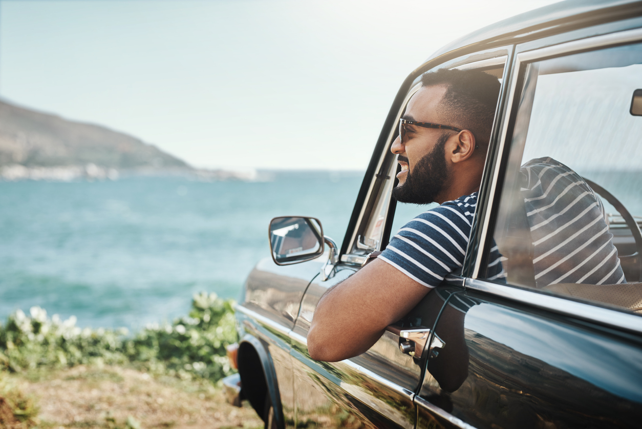 Shot of a young man enjoying a road trip