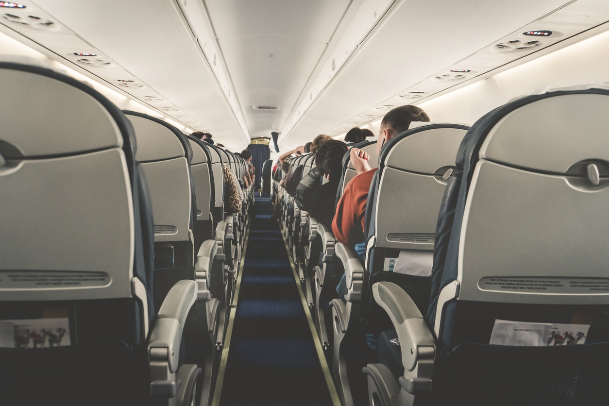 Interior of airplane with passengers on seats waiting to taik off. Horizontal composition. boring flight in economy class aircraft salon. economy class