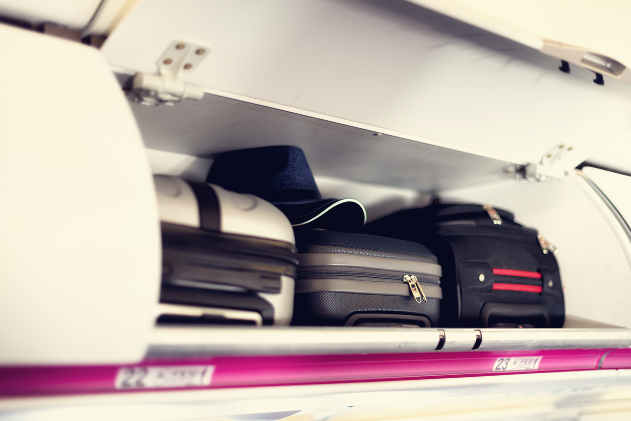 Hand-luggage compartment with suitcases in airplane. Carry-on luggage on top shelf of plane. Travel concept with copy space.