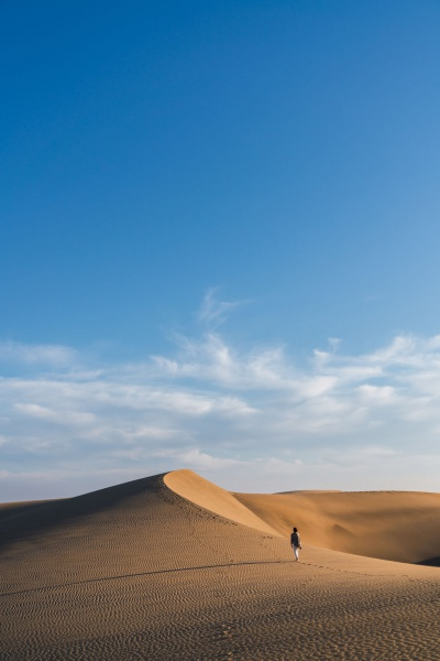 Back view of young woman walking on sand dune between desert and blue heaven in evening in Maspalomas, Spain