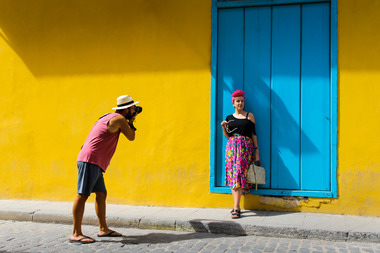 Man taking a photo of a girl in Havana Cuba against a yellow wall