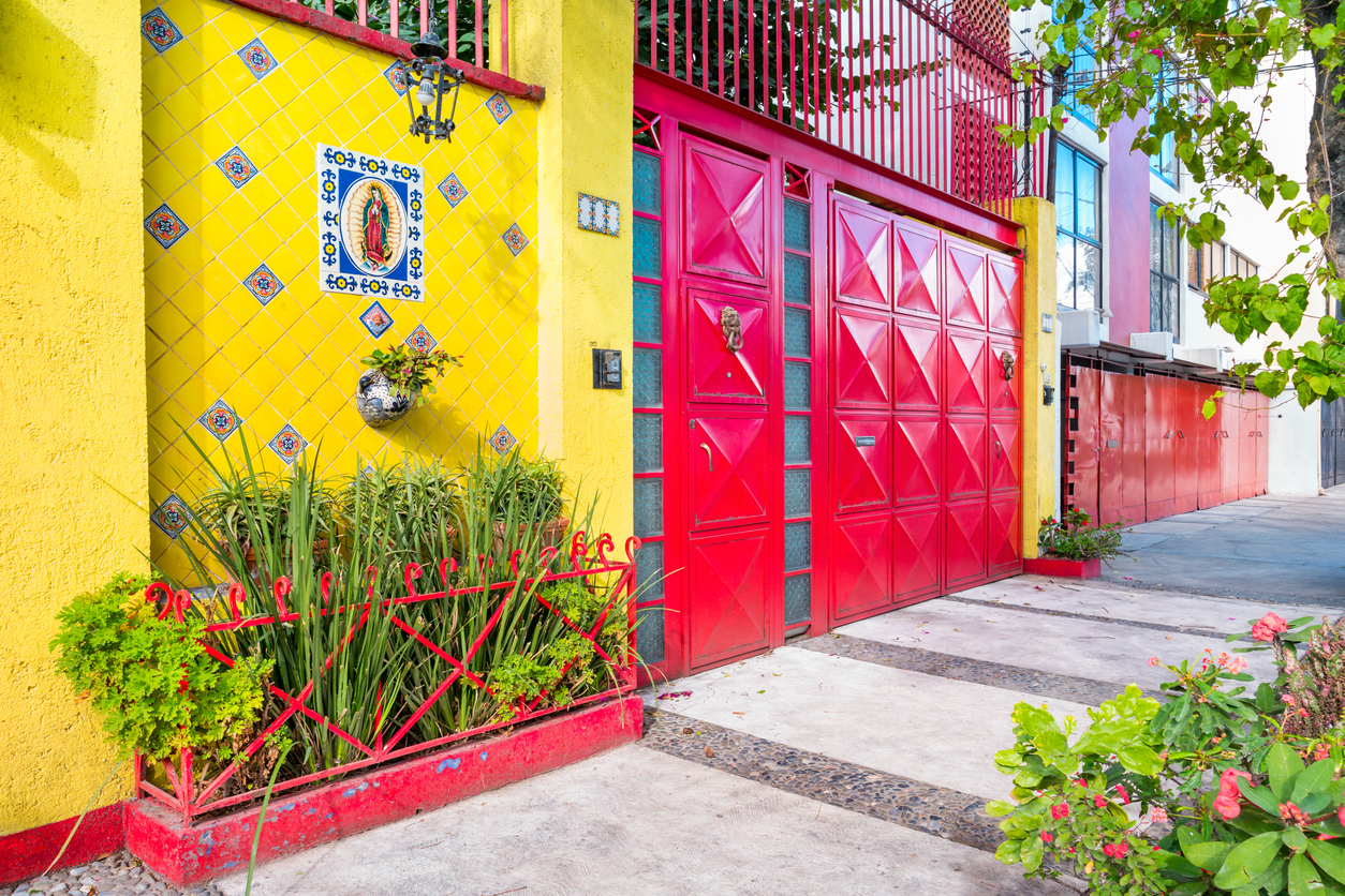 Colorful walls and gates in the historic Coyoacan neighborhood of Mexico City. Coyoacan's tree-lined cobblestone streets, colonial-era estates hidden behind high walls and several interesting churches, museums and artisans' markets make it one of the most pleasant places to visit in the capital.