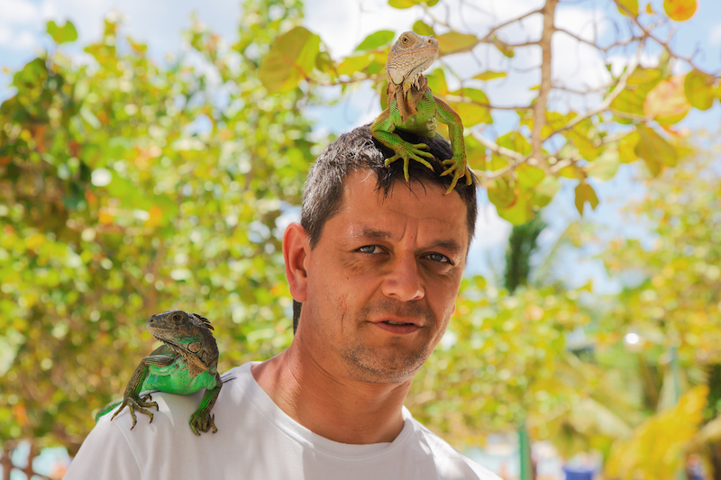 Man with lizards on head and shoulder.