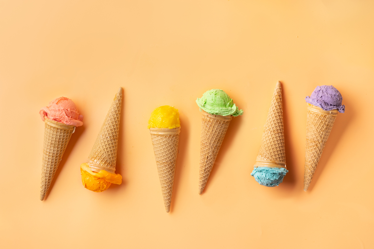 Top view of colorful ice cream cones on yellow backgound. Summer concept