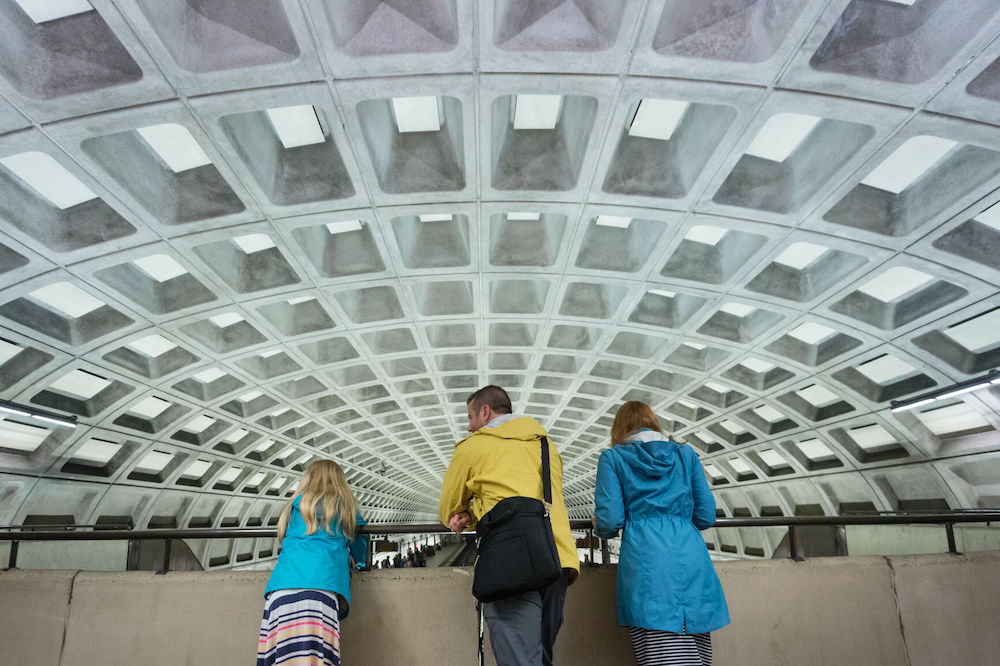 Parents teach daughter about busy public transportation at commuter metro station