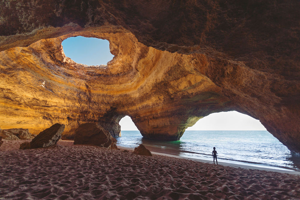 Silhouette of a little boy standing on the enter in Benagil cave on the coast of the Algarve in Portugal.