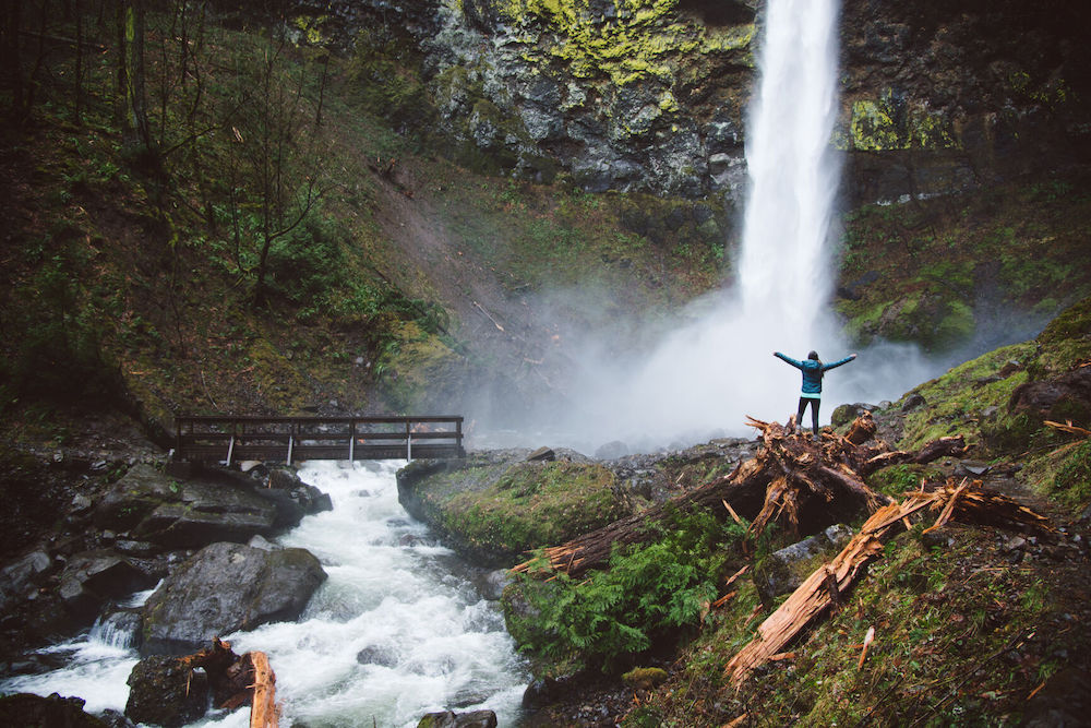 Young woman exploring a beautiful waterfall on a hike in the Columbia River Gorge outside of Portland, Oregon. It is winter but green and lush.