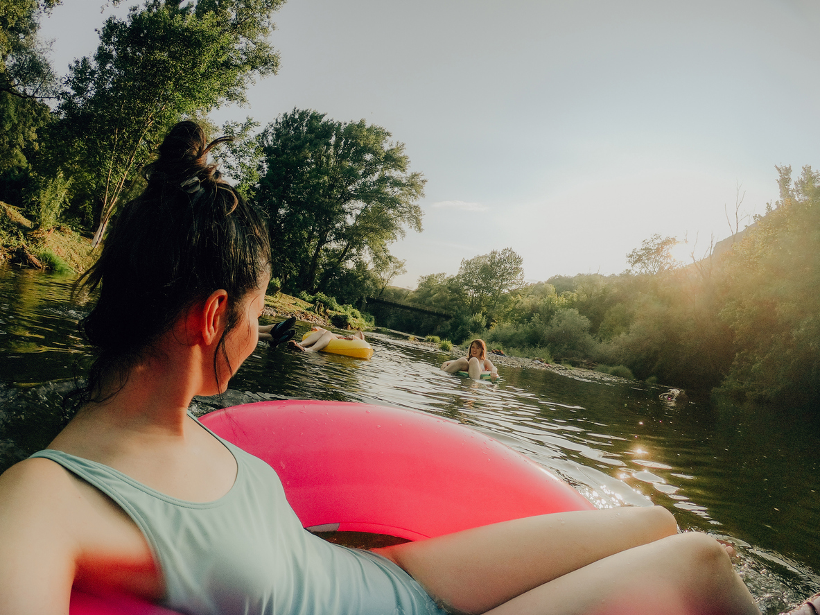 Photo of girlfriends relaxing on inflatable rings in the river