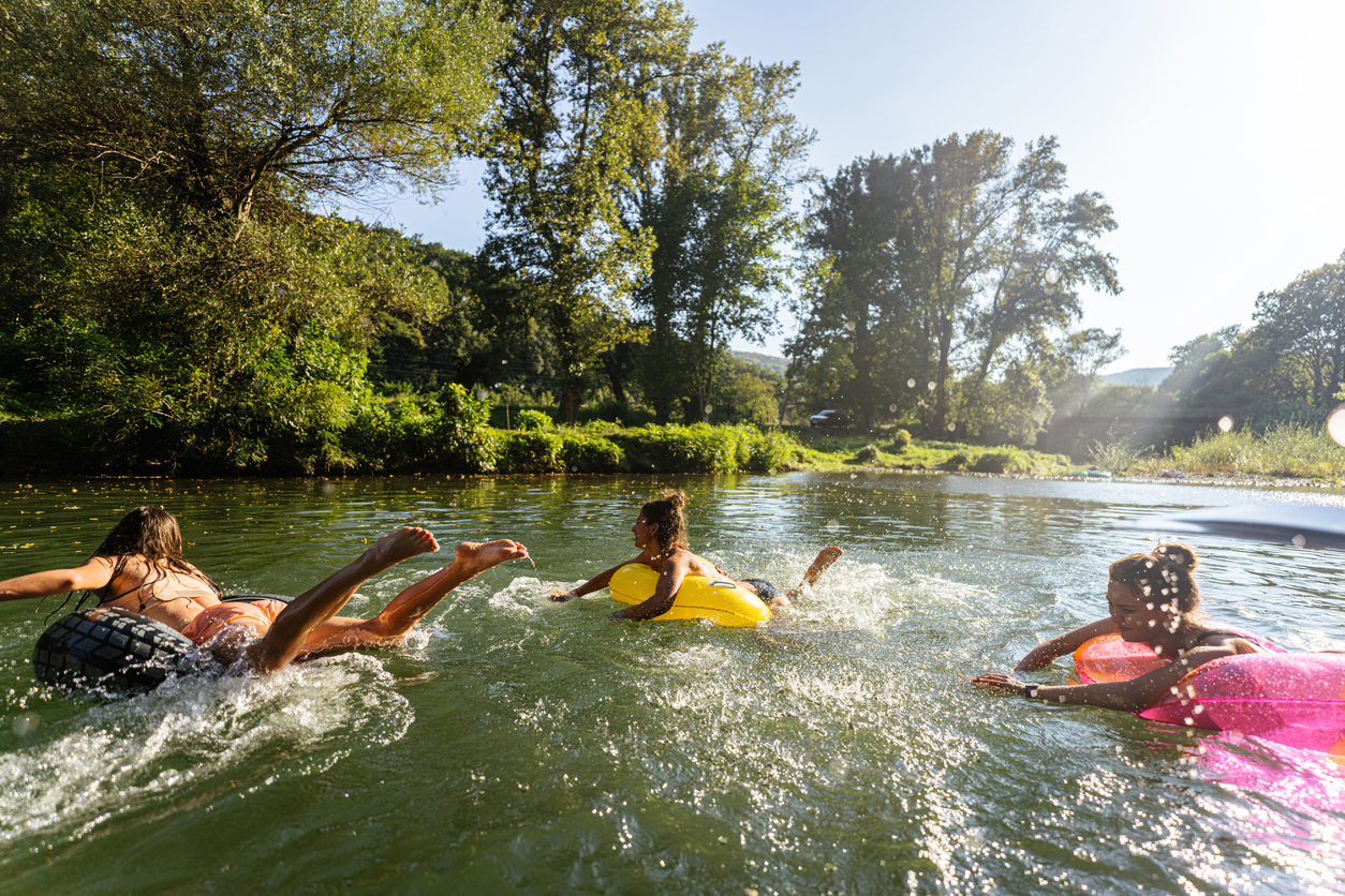 Photo of teenage girls swimming in the river while hanging out in nature; enjoying their youth and friendship and spending a hot summer day outdoors.