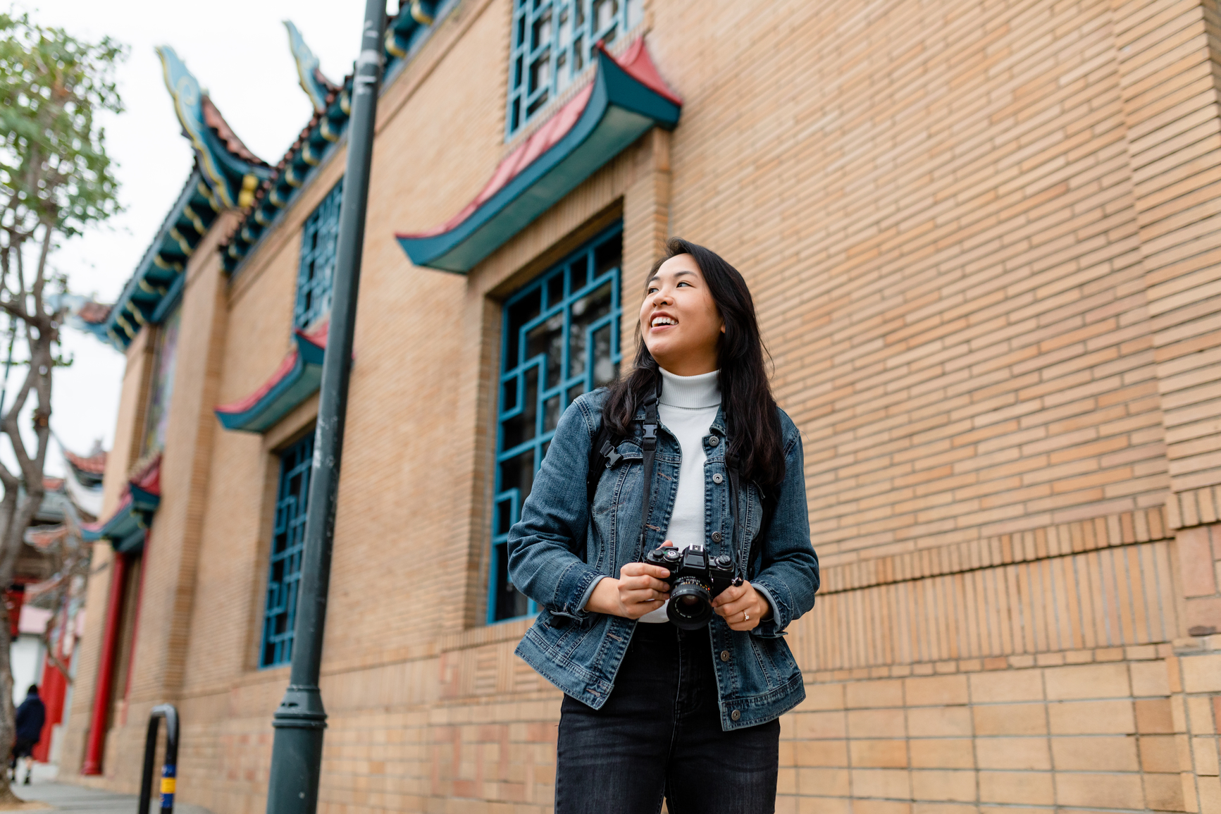 A happy young Asian woman with a film camera around her neck travels solo.