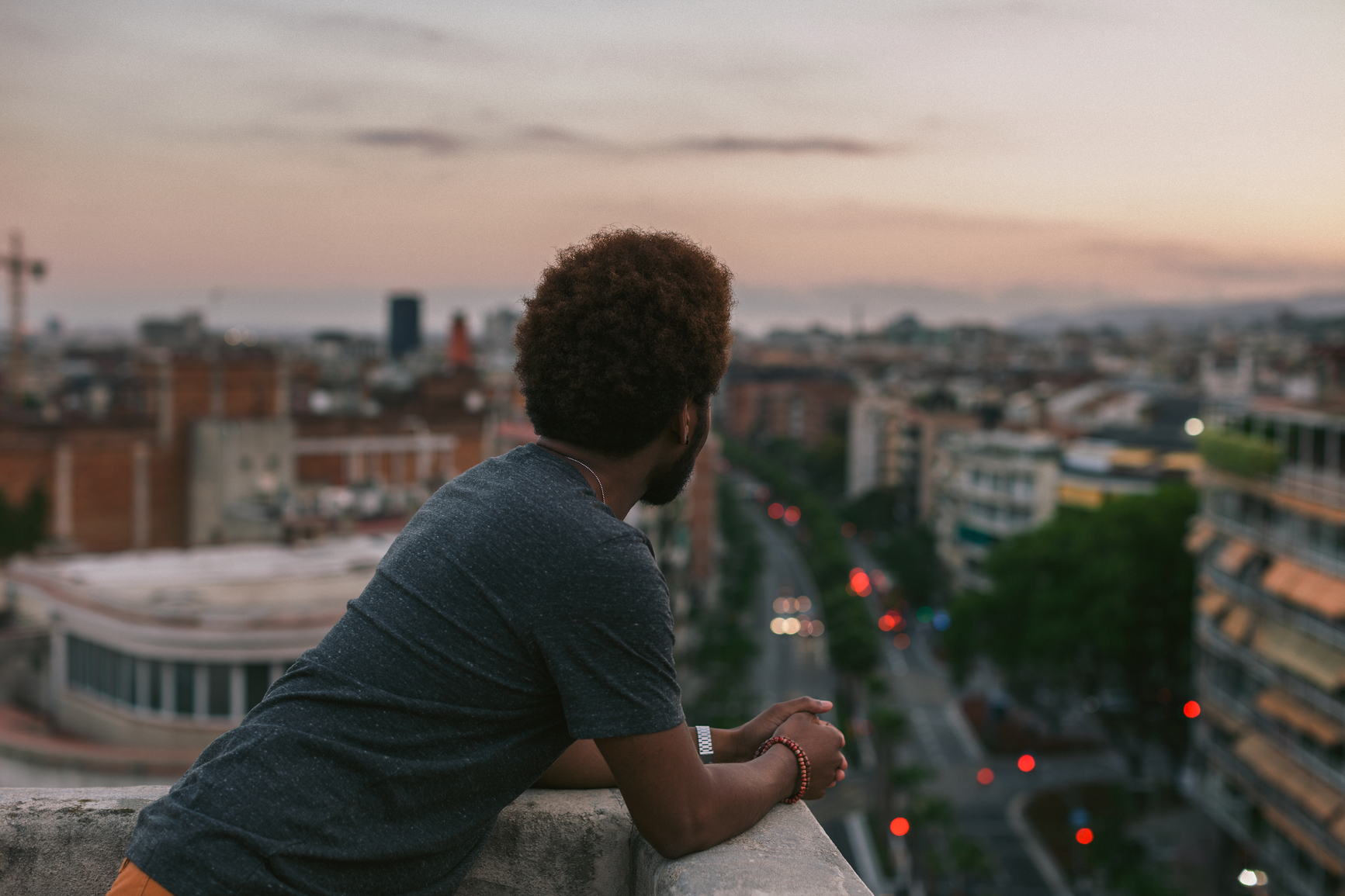 Side View Of A Young African American Man Looking The Barcelona Cityscape On A Rooftop At Sunset.Side View Of A Young African American Man Looking The Barcelona Cityscape On A Rooftop At Sunset.