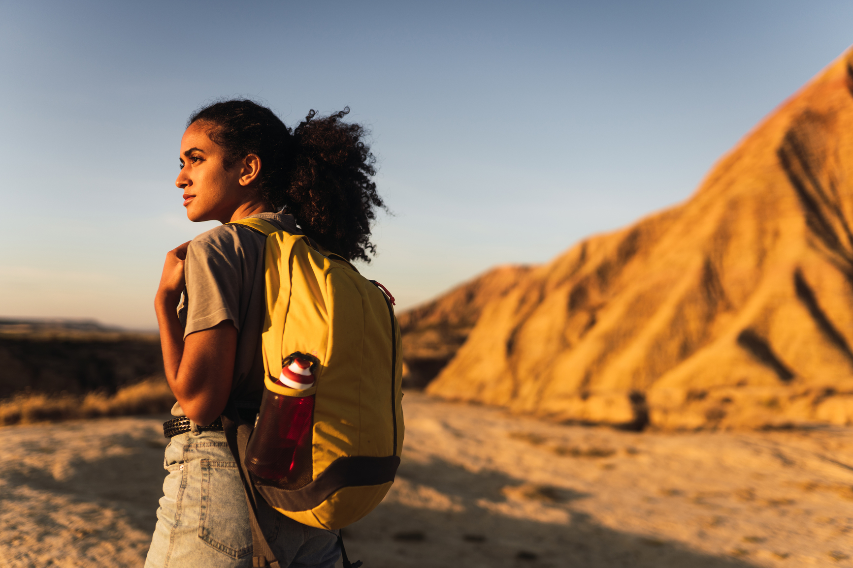 Back view of a woman walking forward in the Navarra desert carrying a yellow backpack. Travel concept