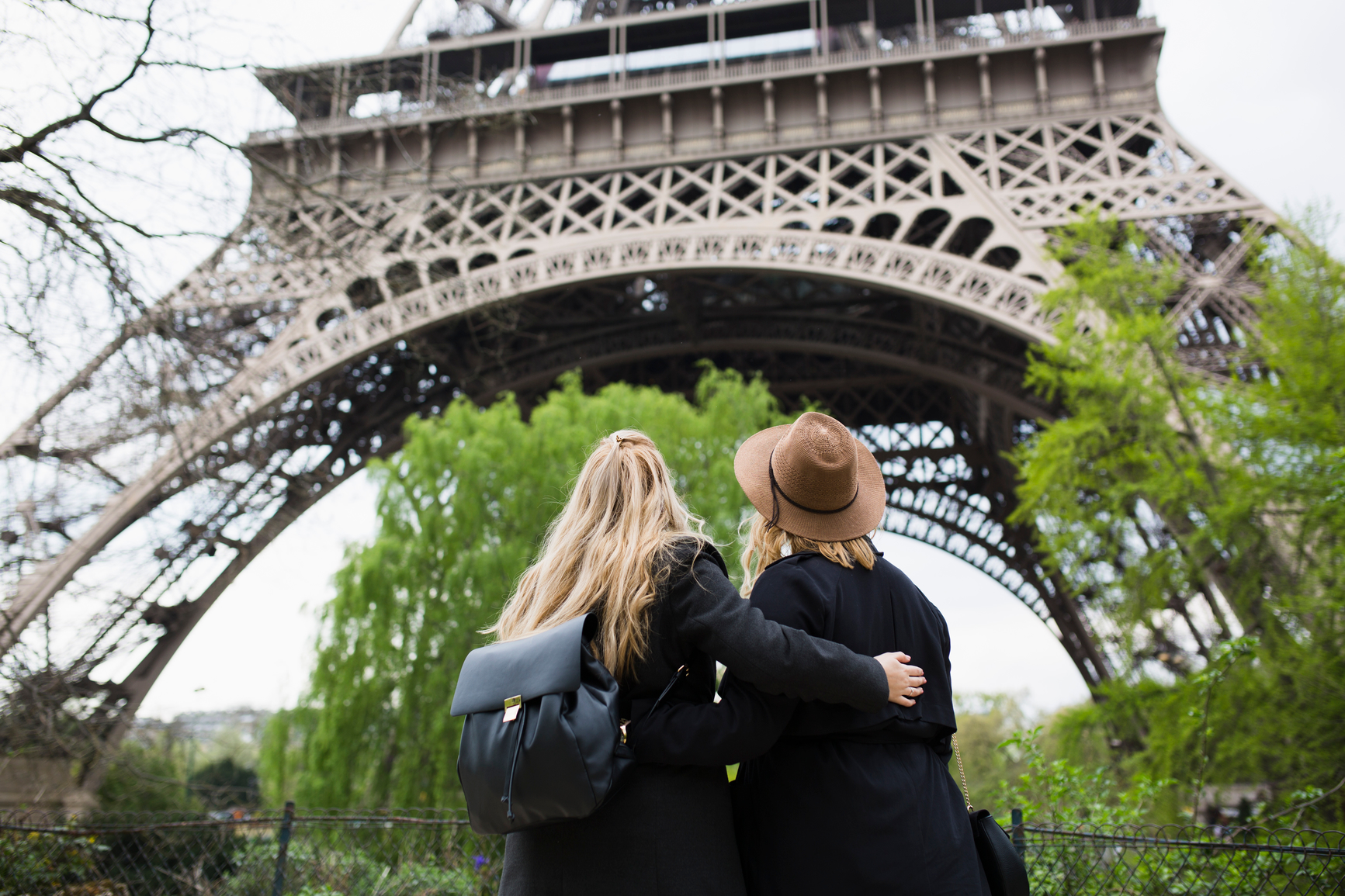 Back view of a two sisters looking at the Eiffel Tower