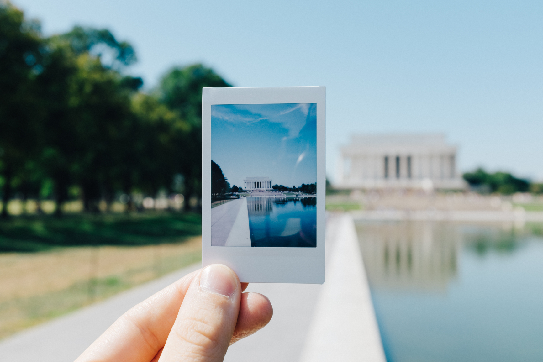 Hand holding a Polaroid of the Lincoln Memorial during a sunny summer day