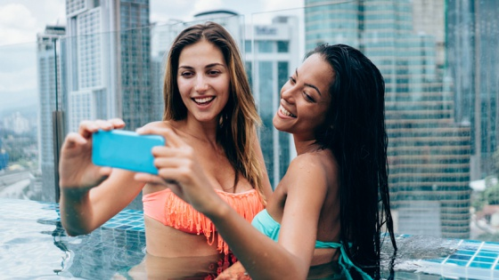 two friends taking a selfie at a rooftop pool