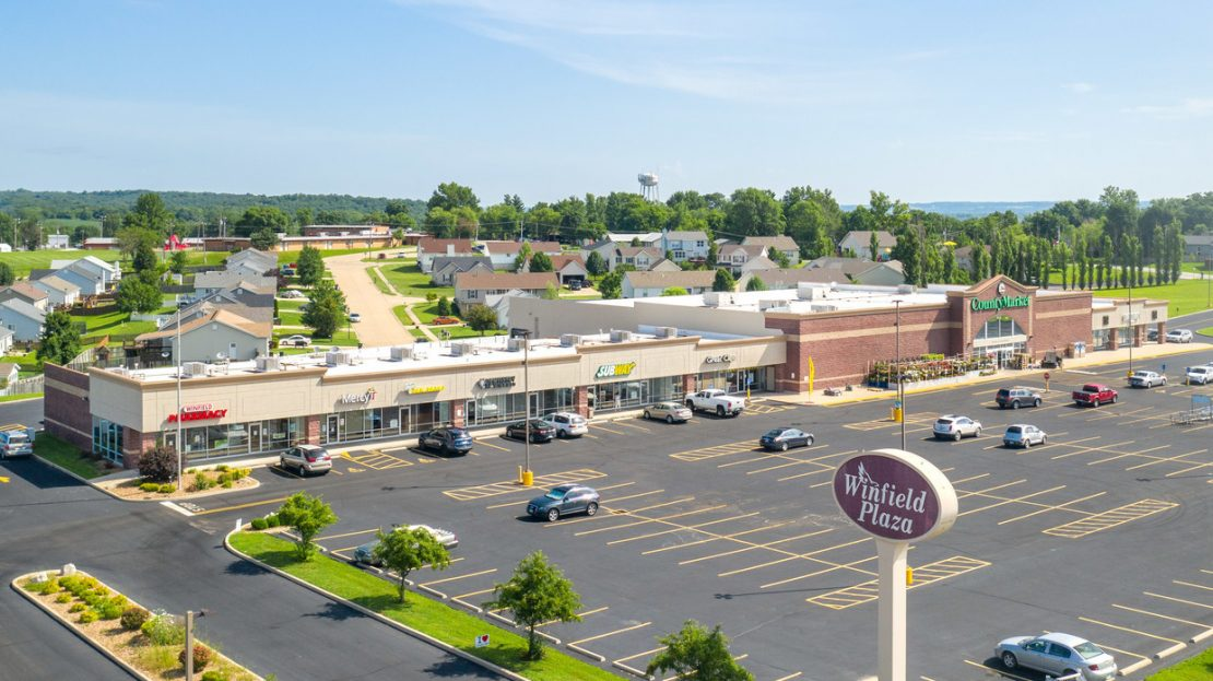Side view of Winfield Plaza Shopping Center with neighborhood in back and parking lot in front.