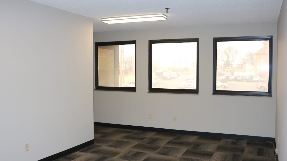 Office inside 1480 Woodstone with white walls, tile carpet and black trimmed windows.
