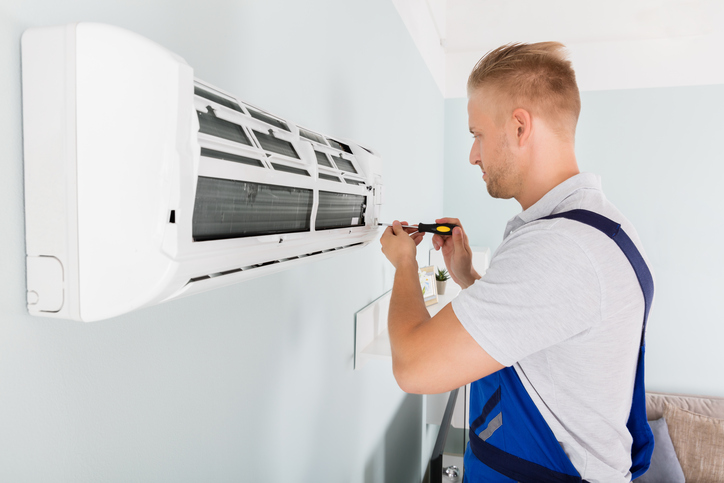 Young Male Technician Fixing Air Conditioner With Screwdriver