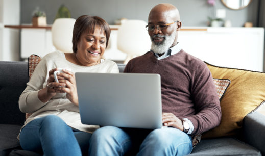Shot of a mature couple using a laptop while sitting together on the couch at home
