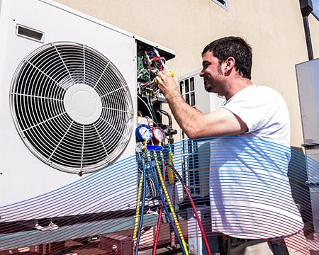 Technician in White Performing A/C Maintenance