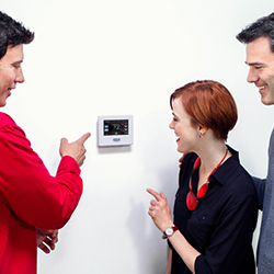 A technician teaching a couple the proper ways to use a thermostat