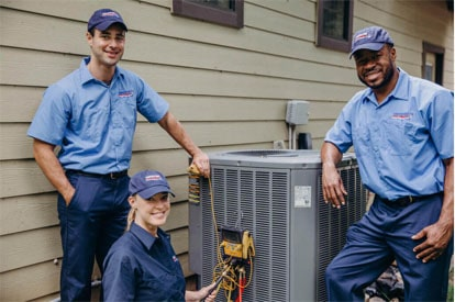 Three technicians fixing an outdoor unit