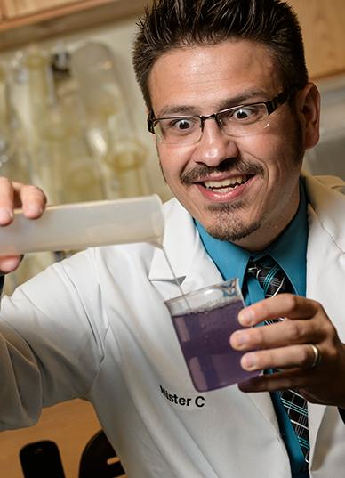 Mister C pouring purple liquid in a beaker