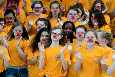 Girls with red clown noses clapping