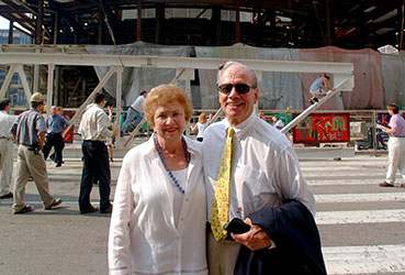 Dr. Benjamin and Marian Schuster standing in front of construction of the Schuster Center