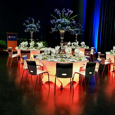 Reception tables set up with dramatic lighting on the Schuster Center stage