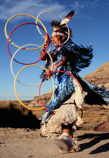 Keven Locke dressed in traditional Native American outfit dancing with hoops