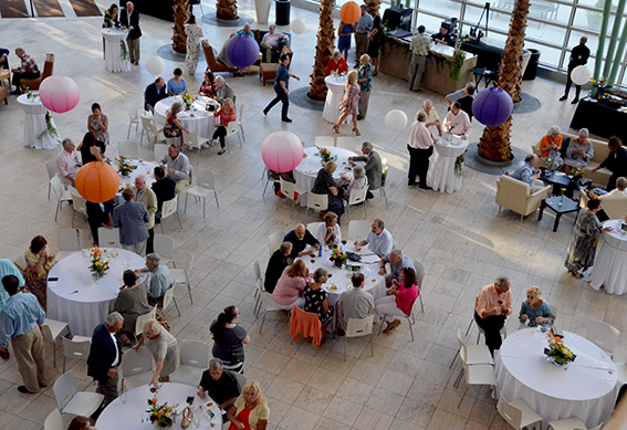 People sitting at tables at an event in the Schuster Center Wintergarden