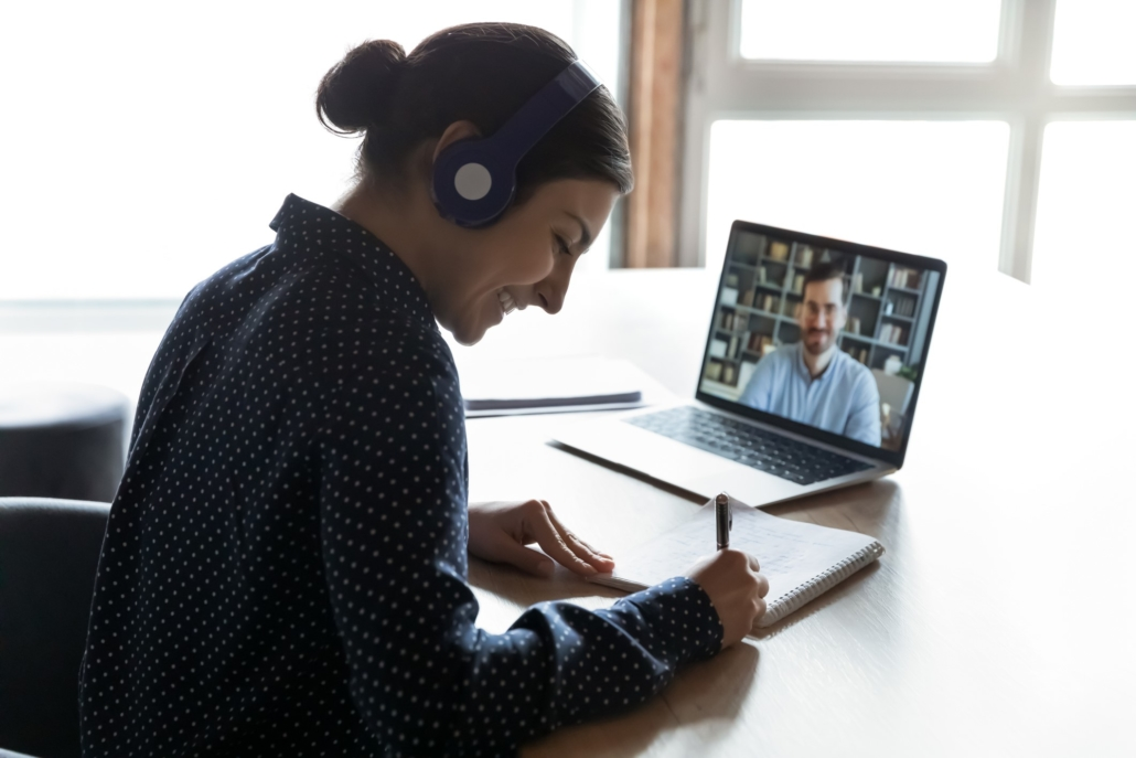 The impact of COVID-19 on software developer training has been mixed. This photo shows a smiling young woman taking notes during a virtual instructor-led training. She is taking part from home, using video conference technology.