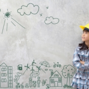 image of a young Asian girl with a hard hat standing in front of a doodle of to express teaching the engineering process to kids