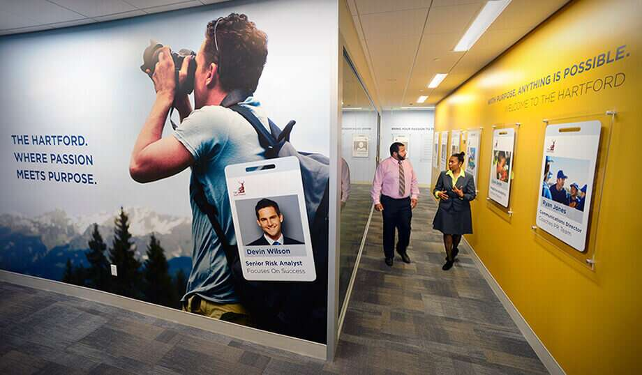 Two people walk through the hallway of a start-up. It is bright and colorful. They discuss reskilling employees.