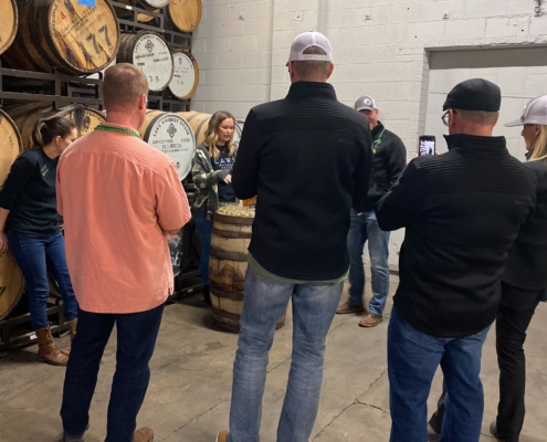 Several DevelopIntelligence employees at a distillery for a team-building event.