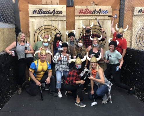 Fourteen DevelopIntelligence employees at an axe-throwing event. This was from a team-building event and it shows our story.