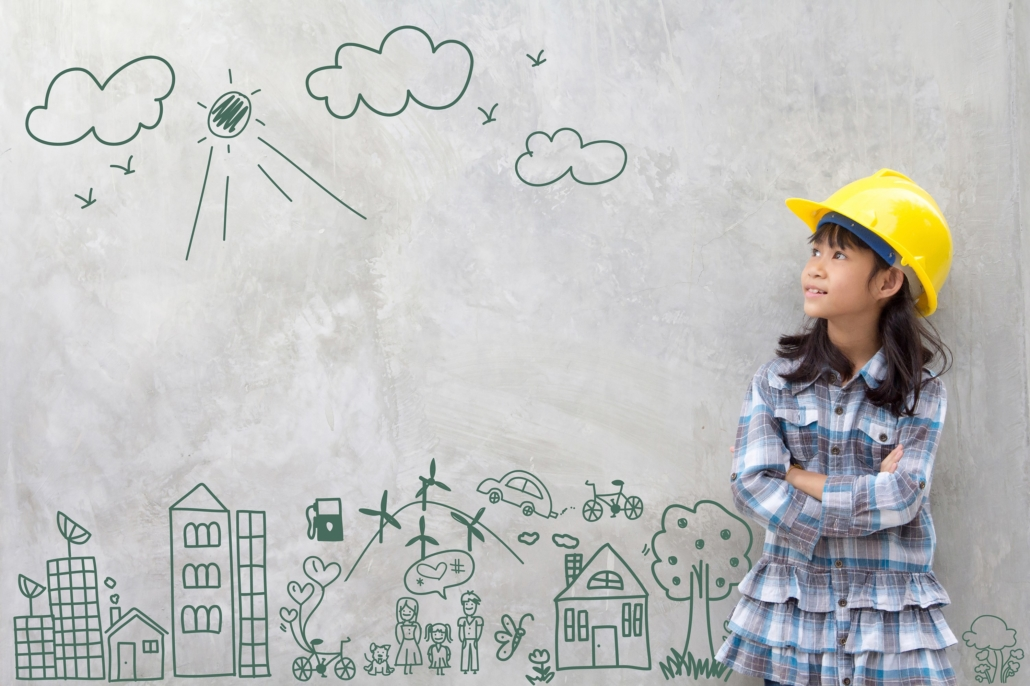 This image shows a young Asian girl wearing a yellow construction hardhat, looking up and to her left. She stands beside a marker drawing of a city scape, sun and clouds. Teaching the engineering process to kids opens their imagination and boosts their willingness to experiment.