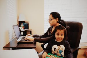 Busy mom working at desk with young daughter