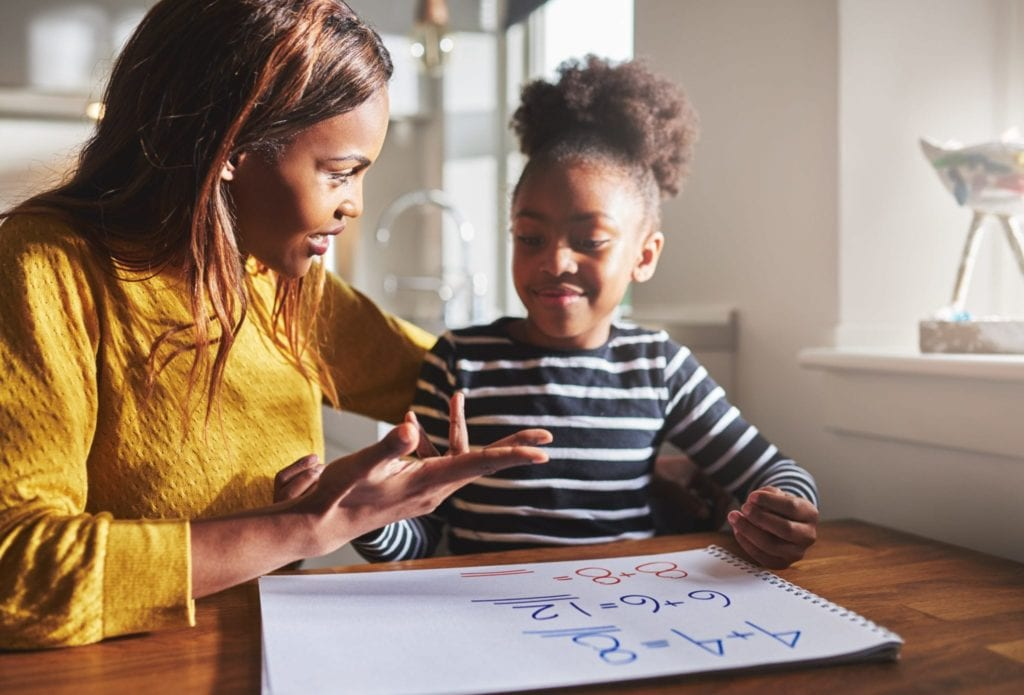 Parent helping daughter on math homework