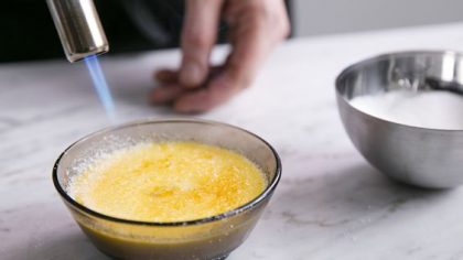 A baker caramelising the sugar atop a creme brulee with a blow torch