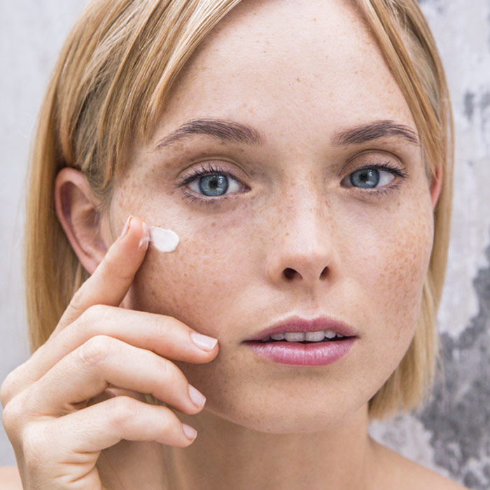 woman applying SATIVA skin cream to her face