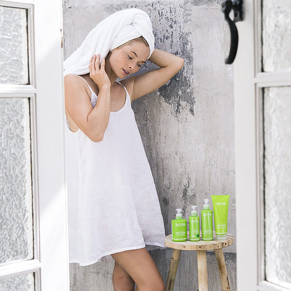 woman admiring a range of SATIVA skincare products