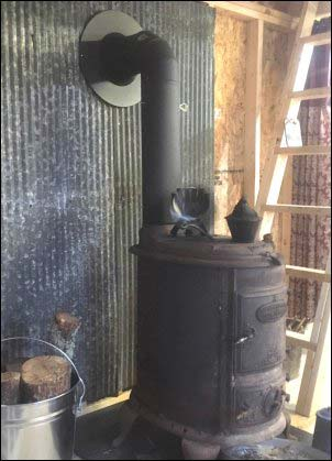 Antique family heirloom wood stove in place in the new portable building cabin