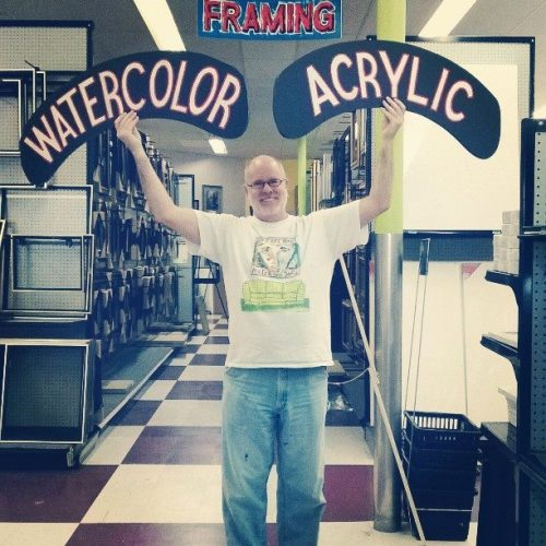 A Staff Member with Watercolor & Acrylic Paint Signs at Jerry's Artarama Art Supply Store in Nashville, TN
