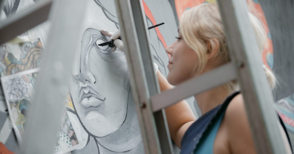woman drawing an eye on a gray painting