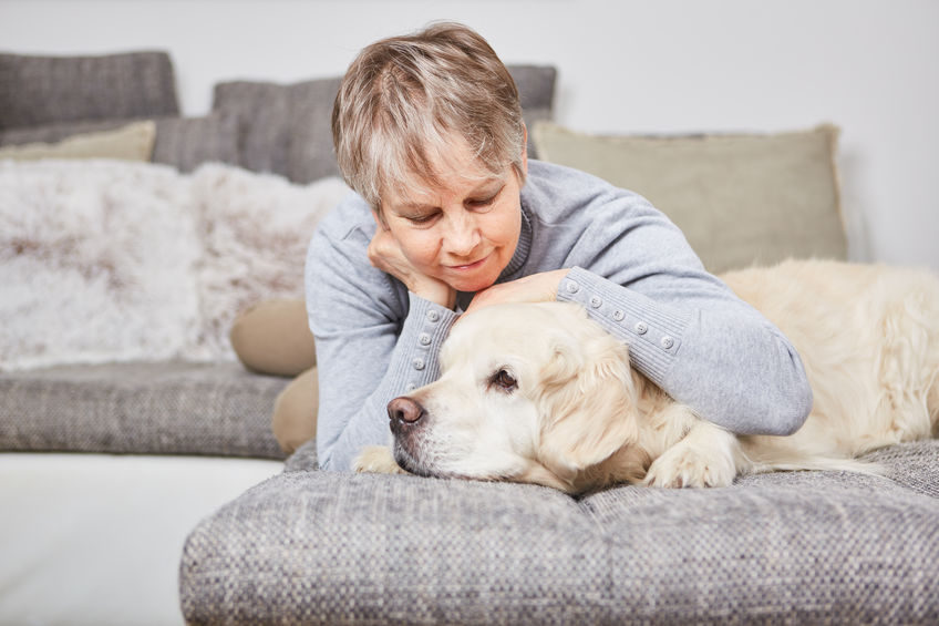 Lonely woman cuddles with dog pet on the couch, benefits of pet therapy