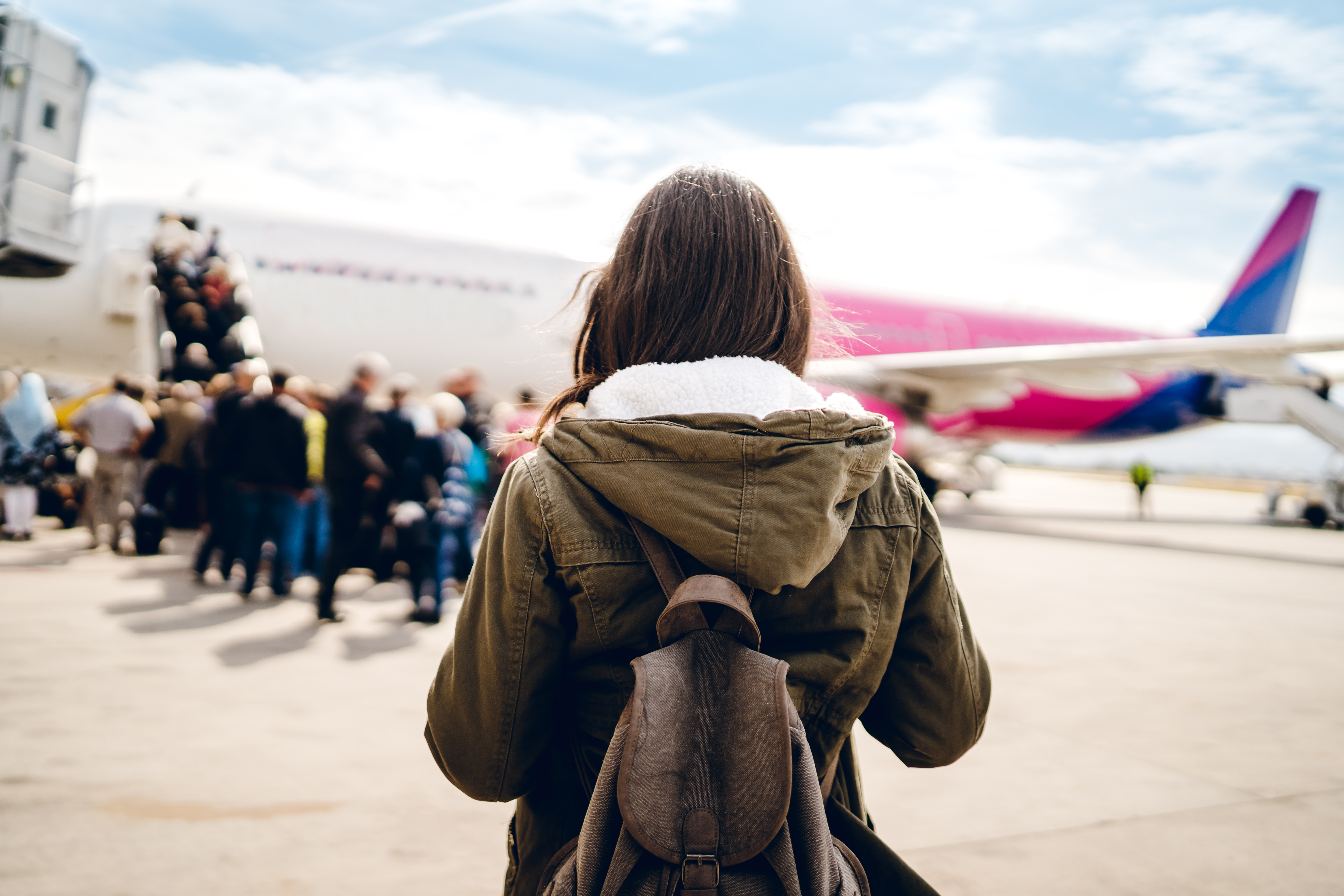 Woman on tarmac lining up to board a plane